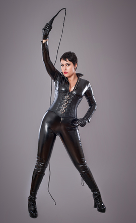 costumes: catwoman. Beautiful woman in catwoman leather latex whith whip