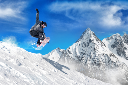Extreme snowboarding man. Snowboarder jumping high in the air