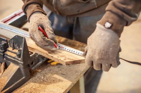 テープ メジャーを使用して建設労働者。木製の板を測定作業でプロの大工