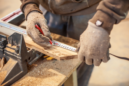 Construction Worker Using Tape Measure. Professional carpenter at work measuring wooden planks