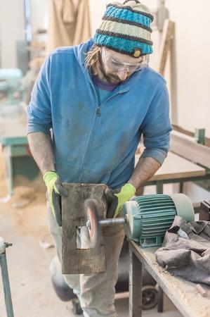 workroom: Carpenter Using Electric Sander. Carpenter sanding a wood with sander