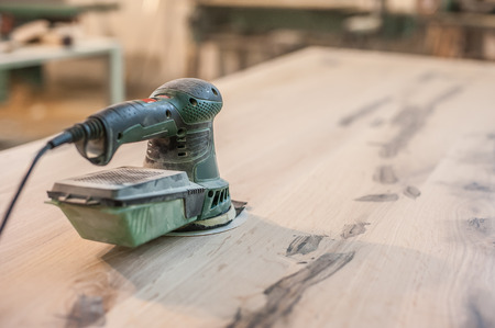 sander: Electric Sander. Carpenter sanding a wood with sander