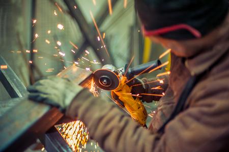 電動グラインダー。鉄骨工場で電動グラインダーを使って取り組んで男火花を散らす