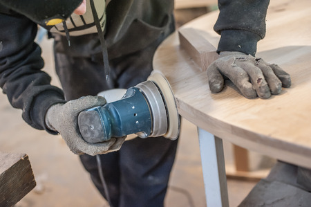 Carpenter Using Electric Sander. Carpenter sanding a wood with sander
