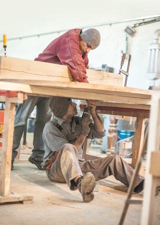woodwork: Man doing woodwork in carpentry. Carpenter work on wood plank in workshop Stock Photo