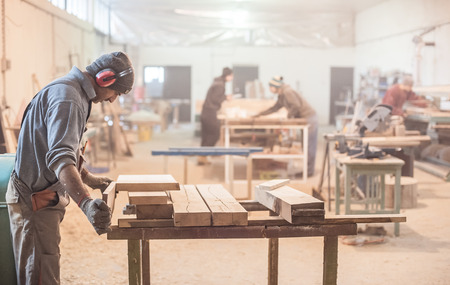 carpentry: Man doing woodwork in carpentry. Carpenter work on wood plank in workshop Stock Photo