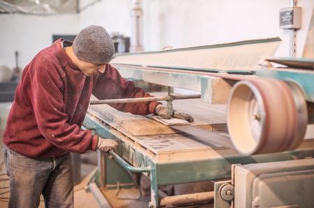 Carpintero que usa la lijadora de banda. Carpintero lijar una madera con lijadora de banda Foto de archivo