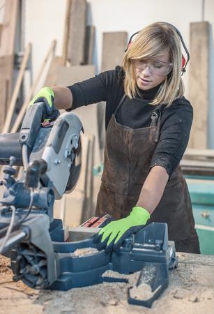 Female carpenter Using Circular Saw. Female carpenter Using Circular Saw for wood