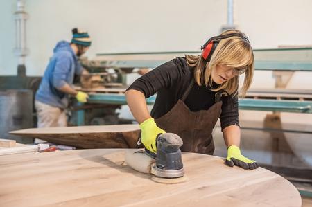 女性の大工を使用して電気研摩機。女性大工の木材を使用して電気研摩機 写真素材