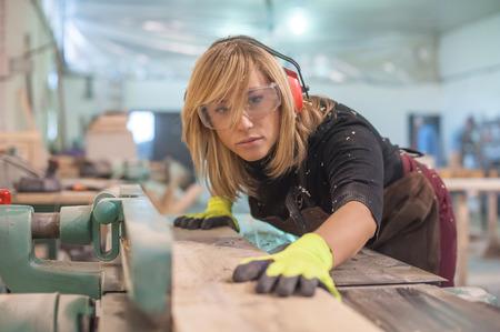 Vrouwelijke Timmerman die elektrische Sander. Vrouw timmerman met behulp van elektrische schuurmachine voor hout Stockfoto