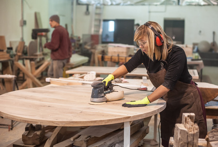 manufactory: Female carpenter Using Electric Sander for wood