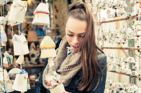 buying: Woman buying souvenirs. Young woman buying souvenirs in gift shop