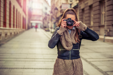 obscured face: Pretty young female tourist photographer taking pictures in the city