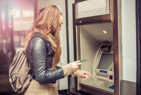 Jonge vrouw die geld van creditcard bij ATM Stockfoto