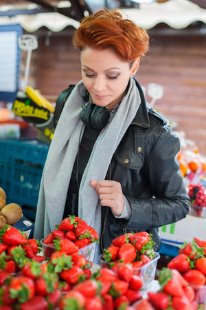 Young woman buys fruits and vegetables on street market Stock Photo