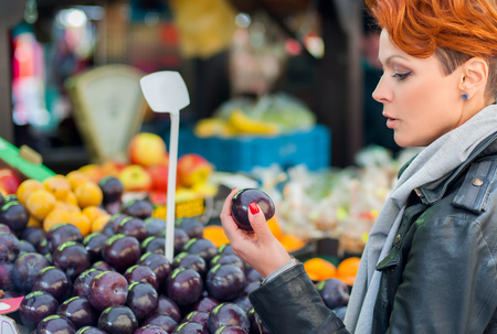 apple gmo: Young woman buys fruits and vegetables on street market Stock Photo
