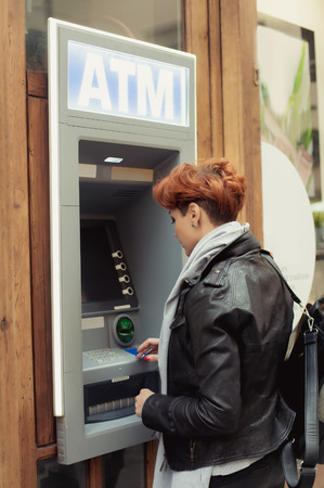withdrawing: Business  woman withdrawing money from credit card at ATM Stock Photo