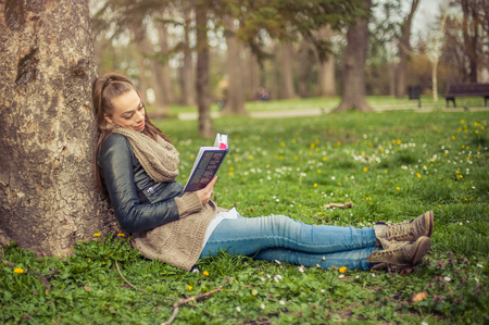 using senses: Beautiful young woman reading book at park