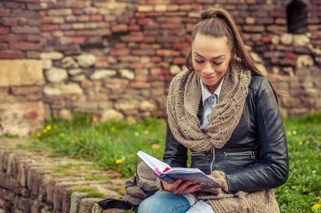 using senses: Beautiful young woman reading book on the wall of fortress Stock Photo