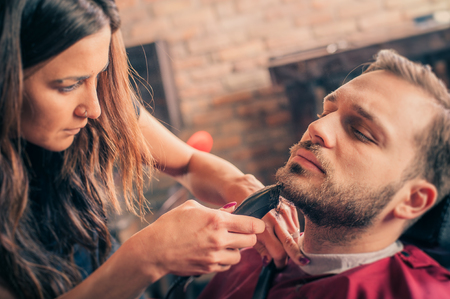 Female barber shaving a clients beard with trimmer in a barber shop
