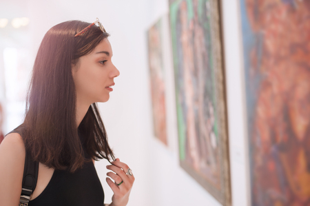Young woman looking at modern painting in art gallery Stock Photo