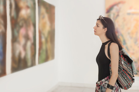 Young woman looking at modern painting in art gallery Banque d'images