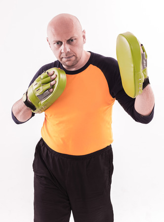 mitts: Martial arts trainer holding focus mitts