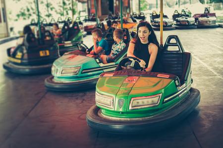 Cute young woman having fun in electric bumper car in amusement park