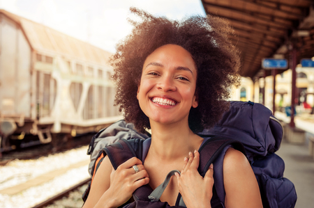over packed: Closeup of beautiful tourist traveler standing with huge luggage at the railway station near the tracks Stock Photo