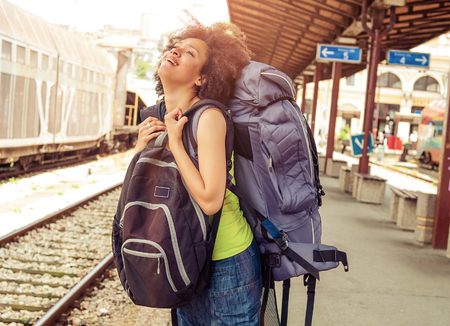 Beautiful tourist traveler standing with huge luggage at the railway station near the tracks Stock Photo
