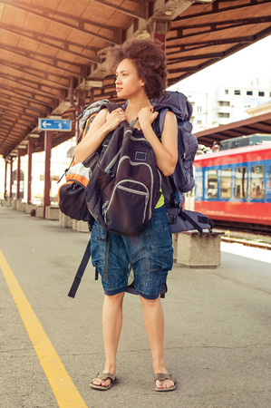 Beautiful tourist traveler standing with huge luggage at the railway station near the tracks Reklamní fotografie