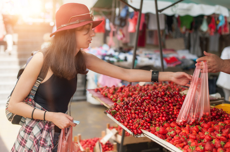 A young woman buying fruits and vegetables at a weekly market. Reklamní fotografie