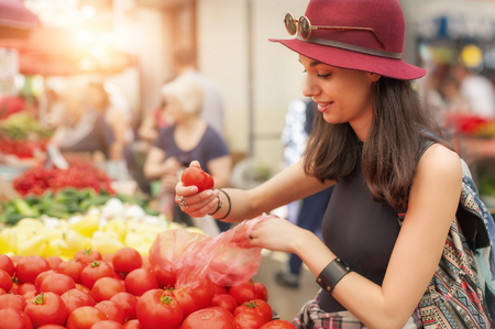 weekly market: A young woman buying fruits and vegetables at a weekly market. Healthy diet Stock Photo
