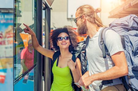 Young tourists looking at city map on the street