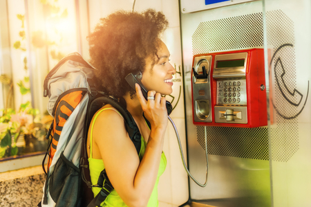 cell phone booth: Portrait of smiling woman using telephone booth Stock Photo