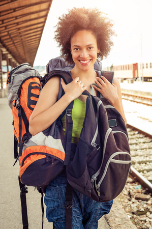 over packed: Beautiful tourist traveler standing with huge luggage at the railway station near the tracks Stock Photo