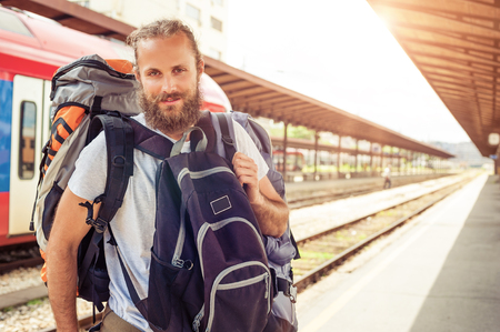 over packed: Handsome tourist traveler standing with huge luggage at the railway station near the tracks