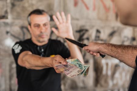 Robber avec un couteau en prenant l'argent de la victime dans une partie abandonnée de la ville