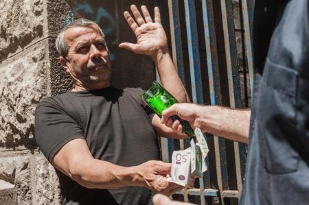 Bully con una botella rota tomar dinero de la víctima en una zona abandonada de la ciudad Foto de archivo