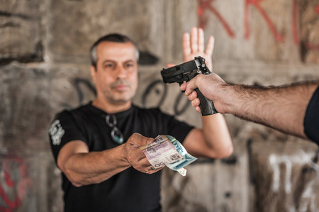 Robber with a gun taking money from victim in a abandoned part of the city Stock Photo