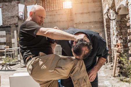 En una lucha de la calle un hombre golpea a otro con la rodilla en la cabeza