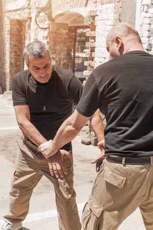 defensa personal: Kapap instructor demuestra técnicas de defensa contra un ataque con arma blanca Foto de archivo
