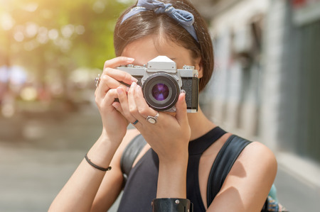 Pretty young female tourist taking pictures in the city Stock Photo