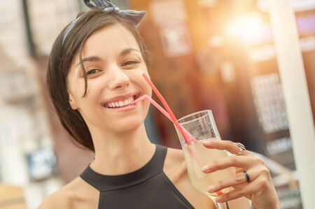 Refreshments: Gorgeous young brunette drinking lemonade, summer heat refreshment Stock Photo