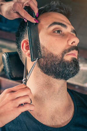 Female barber beard cut a client's beard with clippers in a barber shop. Close-up Stockfoto