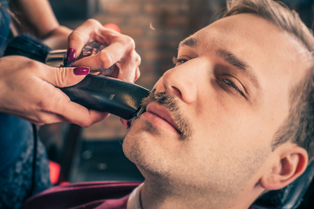 fade: Female barber cut a clients mustache with trimmer in a barber shop. Close-up