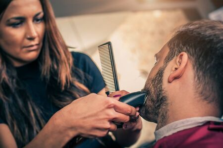 fade: Female barber beard cut a clients beard with trimmer in a barber shop. Close-up