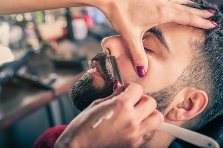 Female barber shaving a client's beard in a barber shop. Close-up