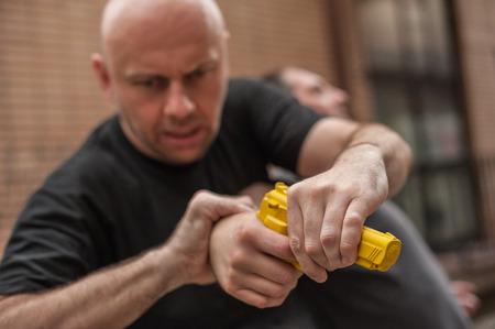 educadores: Kapap instructor demuestra técnicas de defensa contra un arma Foto de archivo