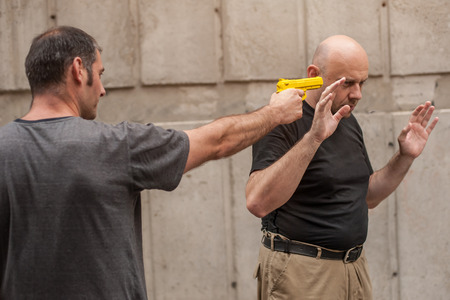 defensa personal: Kapap instructor demonstrates self defense techniques against a gun Foto de archivo
